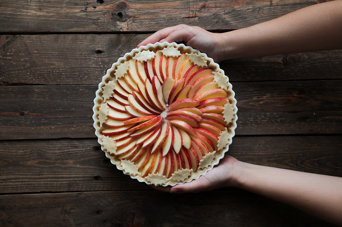 Unrecognizable woman showing a tasty apple pie on a wooden table