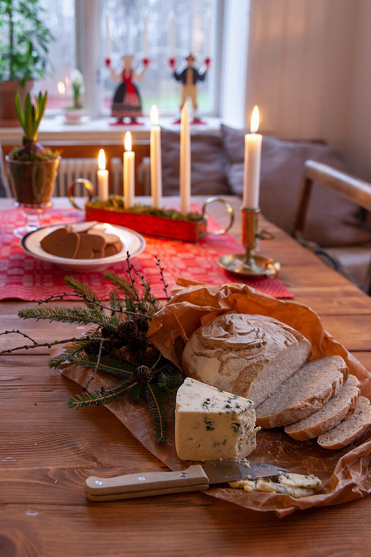 Bread, cheese and pastries on festively set, rustic wooden table