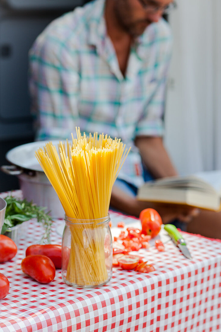 Spaghetti and tomatoes on a kitchen table
