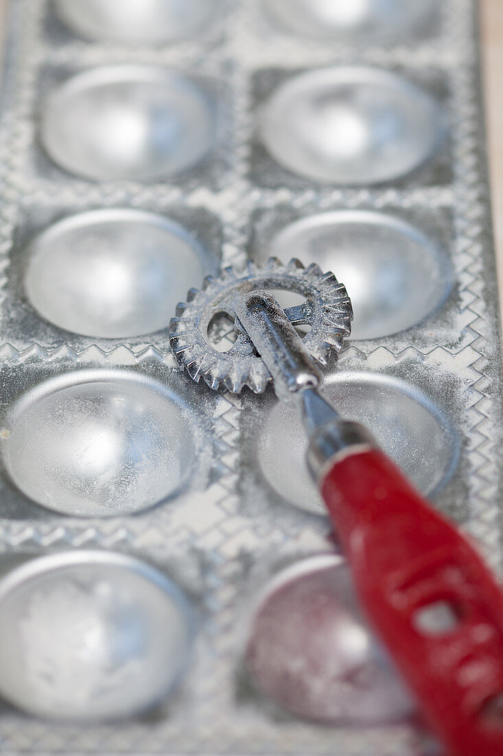 A metal mould for ravioli with a pastry wheel