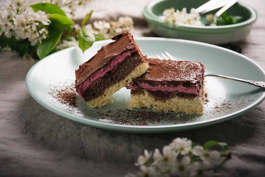 Vegan tray bake cake with a vanilla and chocolate base, sour cherries, sour cherry cream and dark chocolate glaze