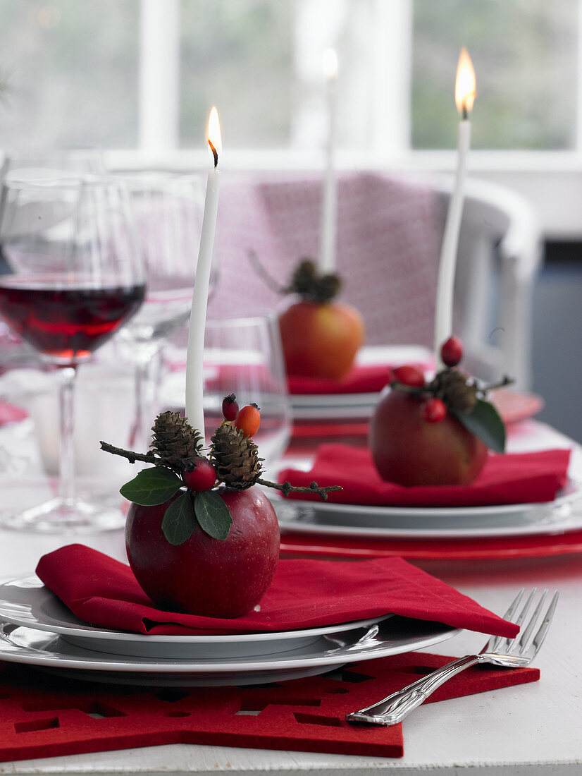Candles and small arrangements on apples on set table