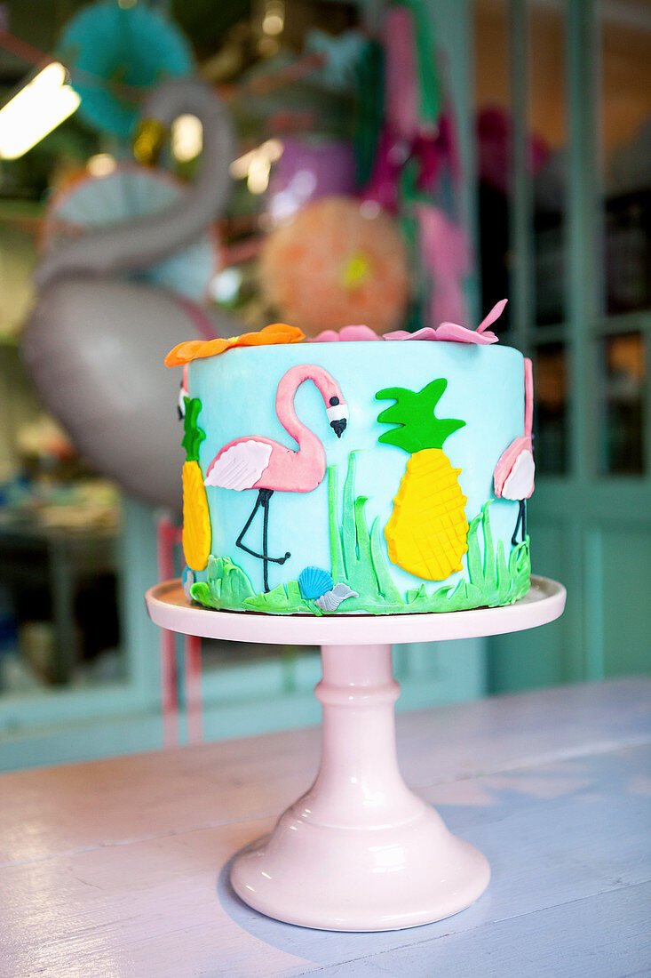 Cake ornately decorated with flamingo and pineapple motifs