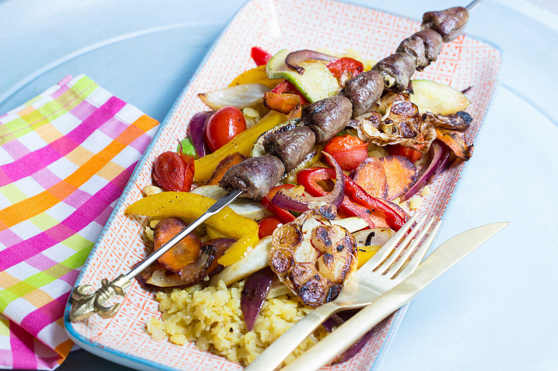 Chicken heart skewer on colourful roast vegetables with yellow lentils