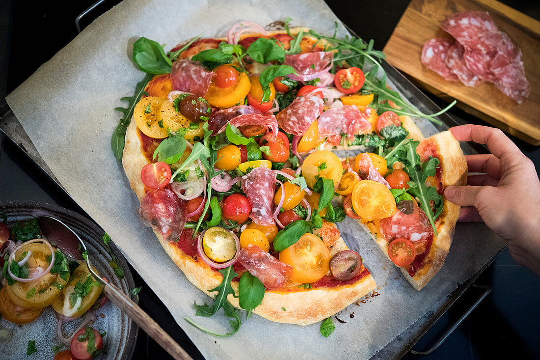 Eating Pizza with tomatoe salad with truffle salami