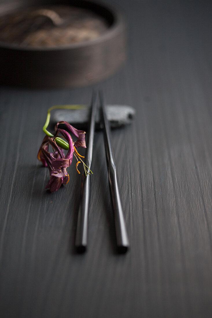 Black chopsticks next to dried gloriosa lily