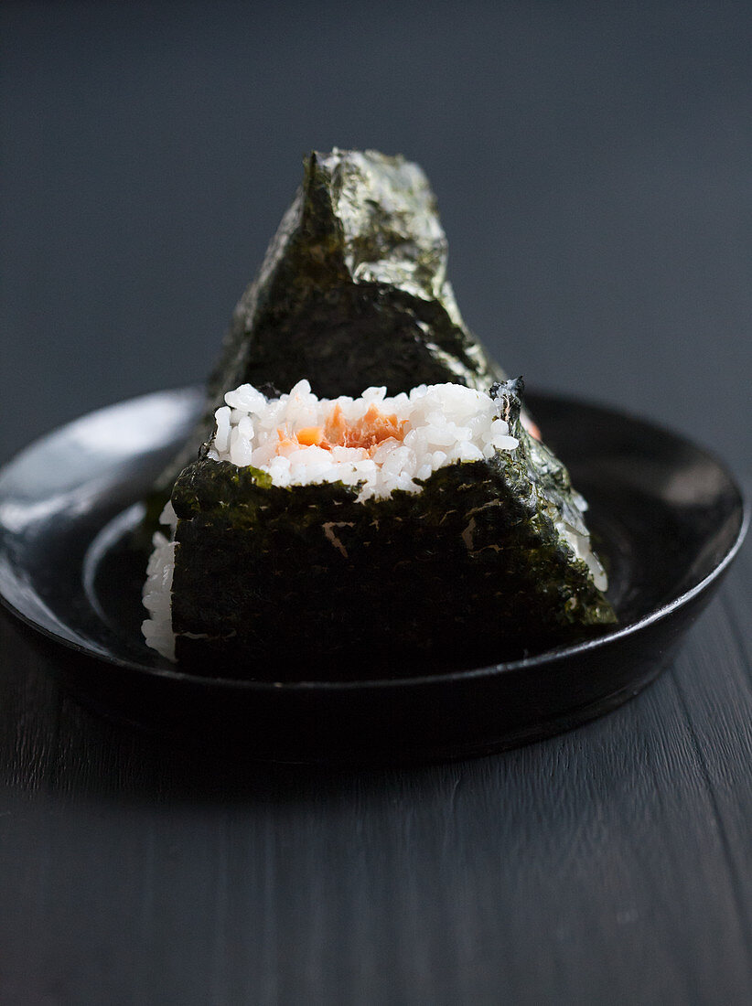Two onigiri filled with salmon, one bitten (Japan)
