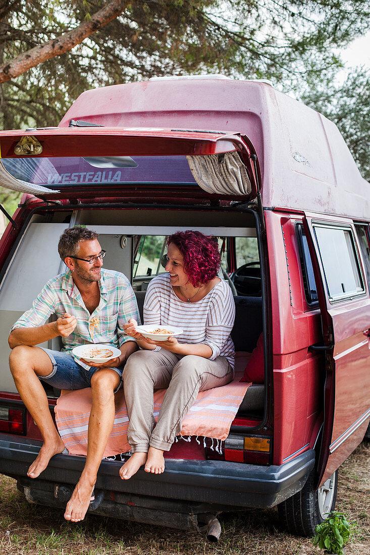 Paar isst Spaghetti im Campingwagen