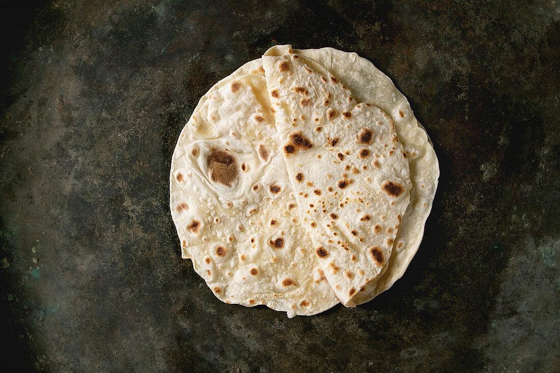 Homemade pita or chapati flatbread flapjack over dark metal background
