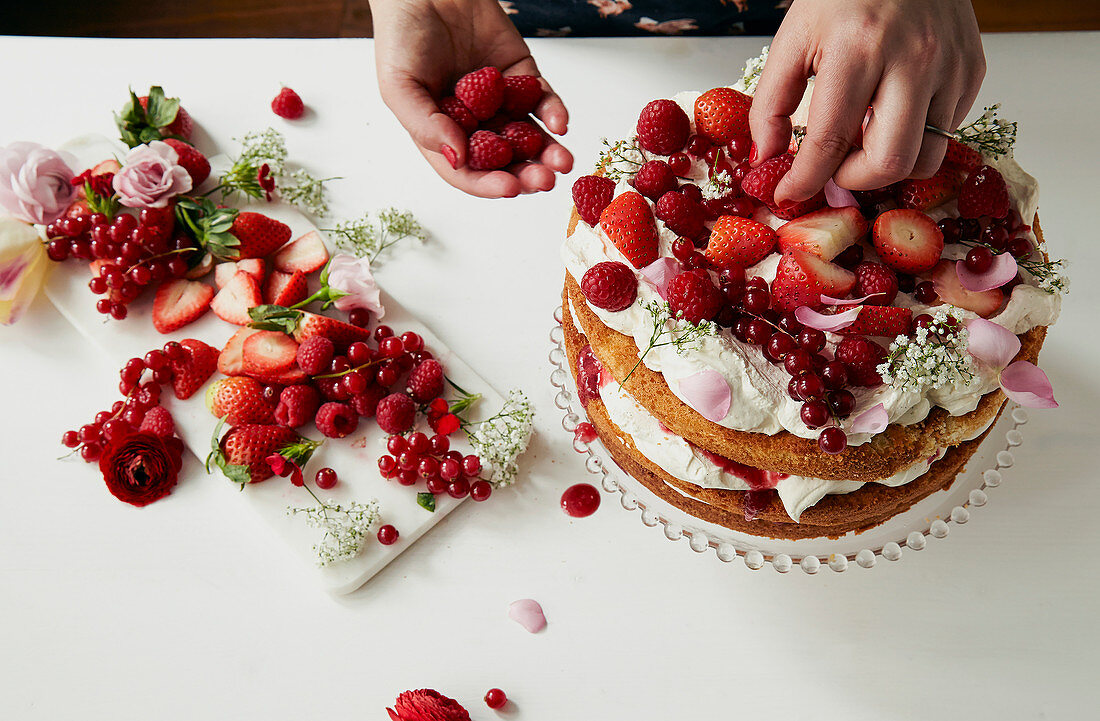 Victoria Sponge layer cake being decorated and filled with fresh cream and fruit coulis