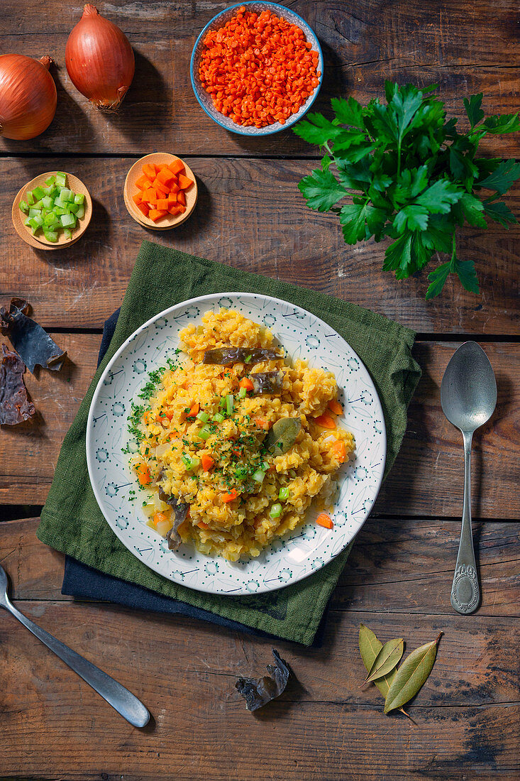 Plate of delectable vegan pilaf with carrot and onion and spiced with bay leaves and parsley against lumber tabletop