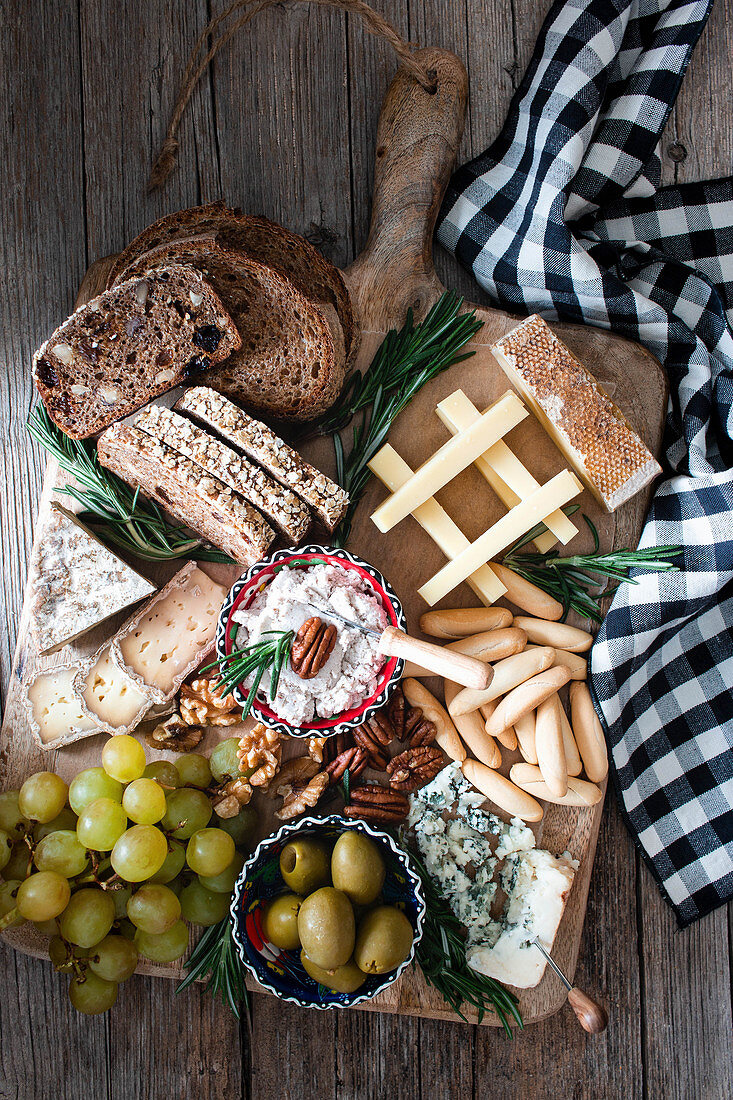 Composition of fresh rye bread, cheese, grape bunch and olives placed on wooden board