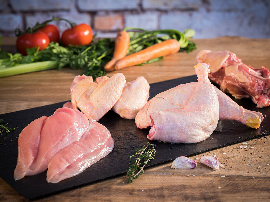 Fresh chicken, divided into breasts, drumsticks, wings and carcasses, with soup vegetables behind