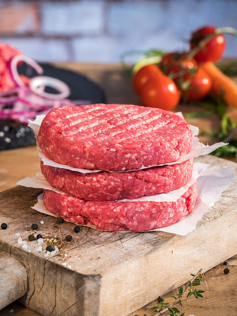 Raw hamburger patties, vegetables and spices