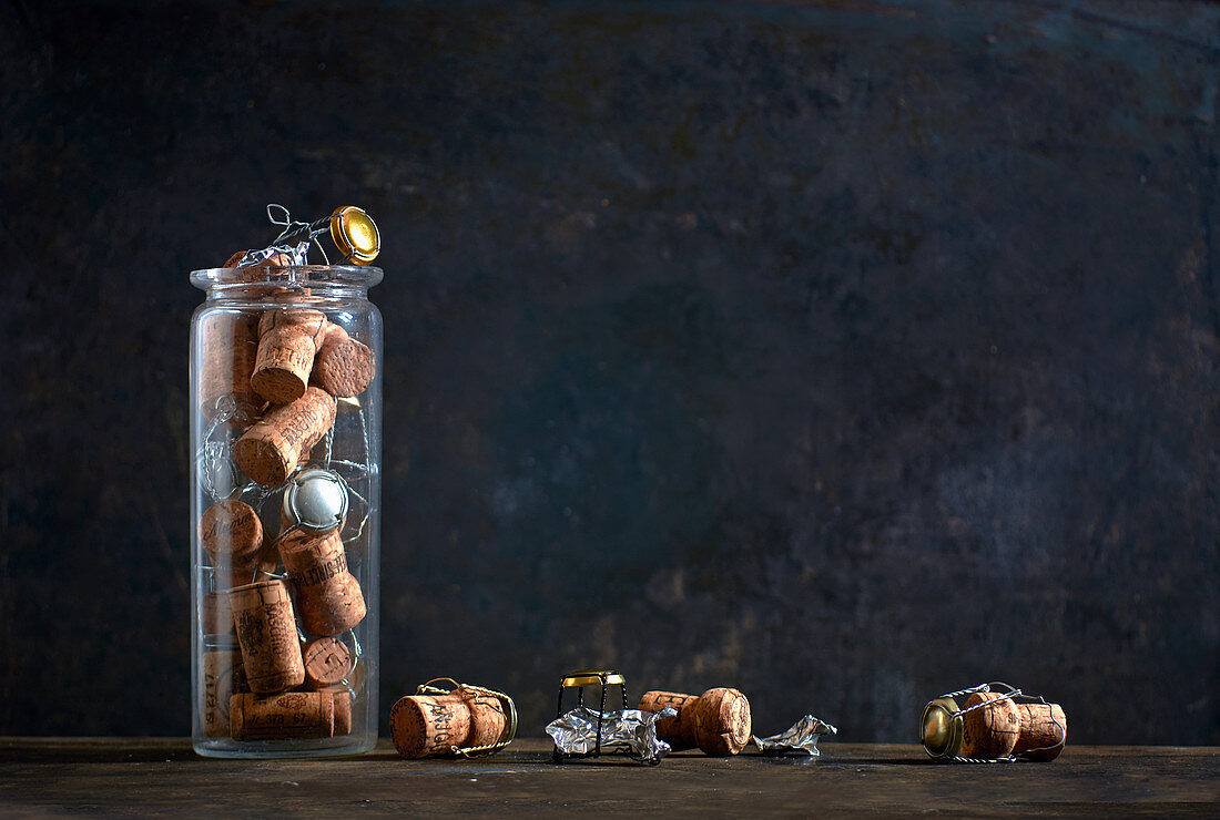 Several champagne corks and agraffes in and beside a mason jar