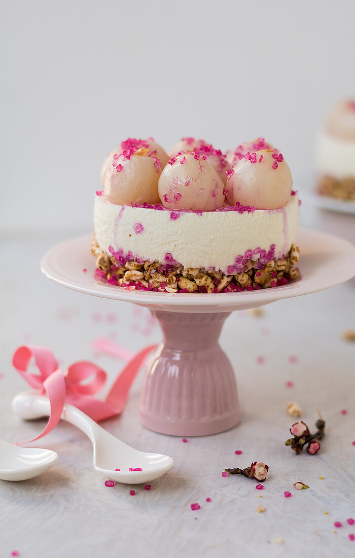 Cheesecake with lychees on a cake stand
