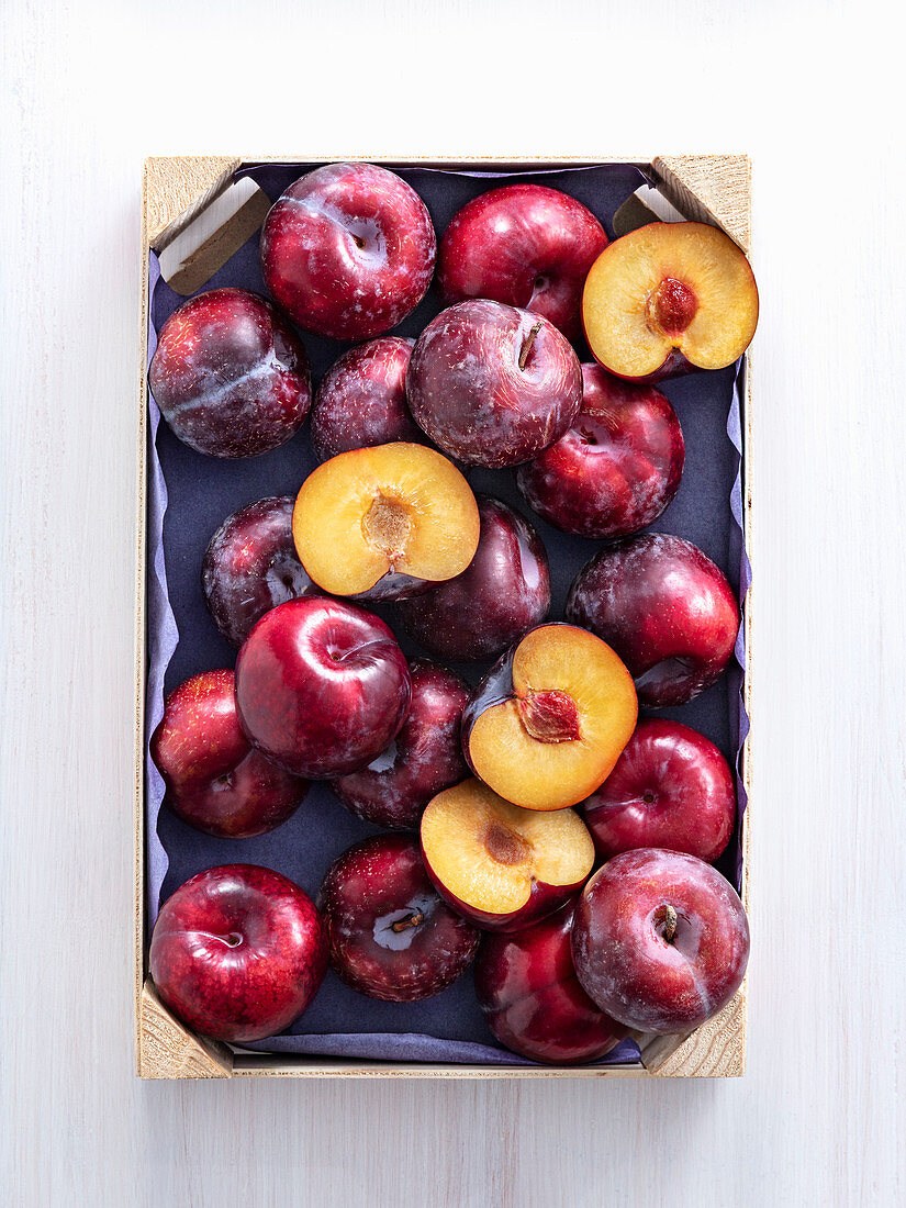 Red plums in a wooden crate, some halved