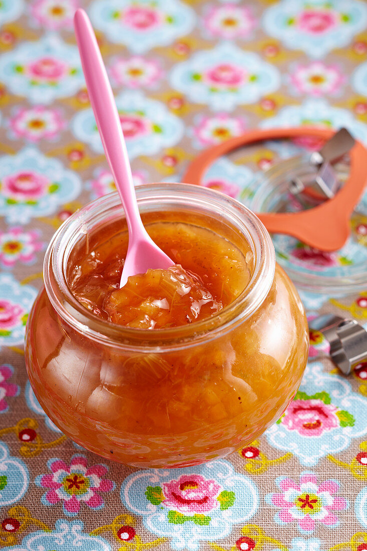 Rhubarb and melon jam in a mason jar with a plastic spoon