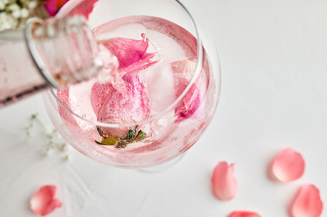 Pouring rose infused tonic for the gin and tonic cocktail