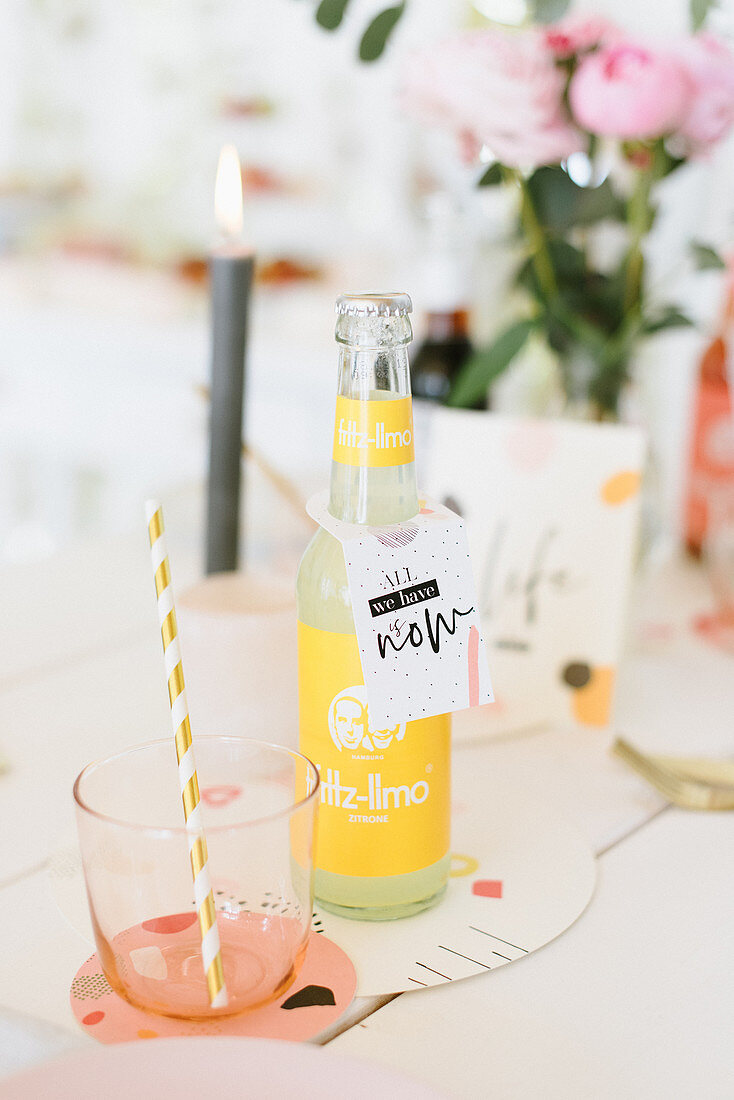 Bottle of lemonade and glass with straw on festively set table