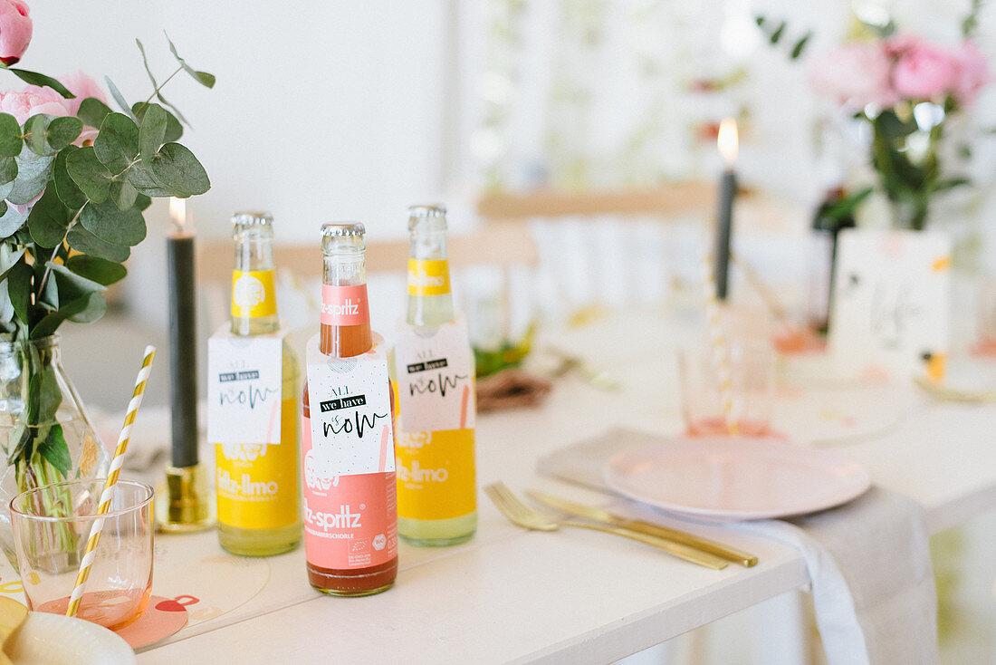 Various bottles of lemonade on festively set table