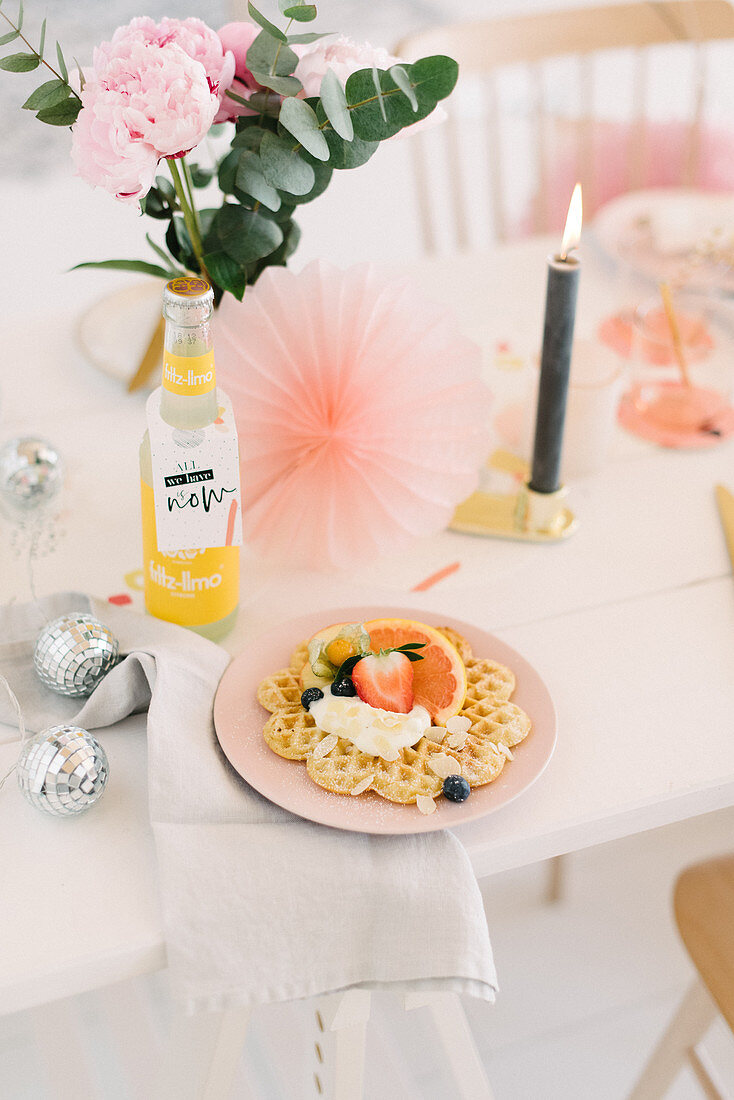 Waffle and fruit on table festively decorated with glittery balls, candle and paper rosettes