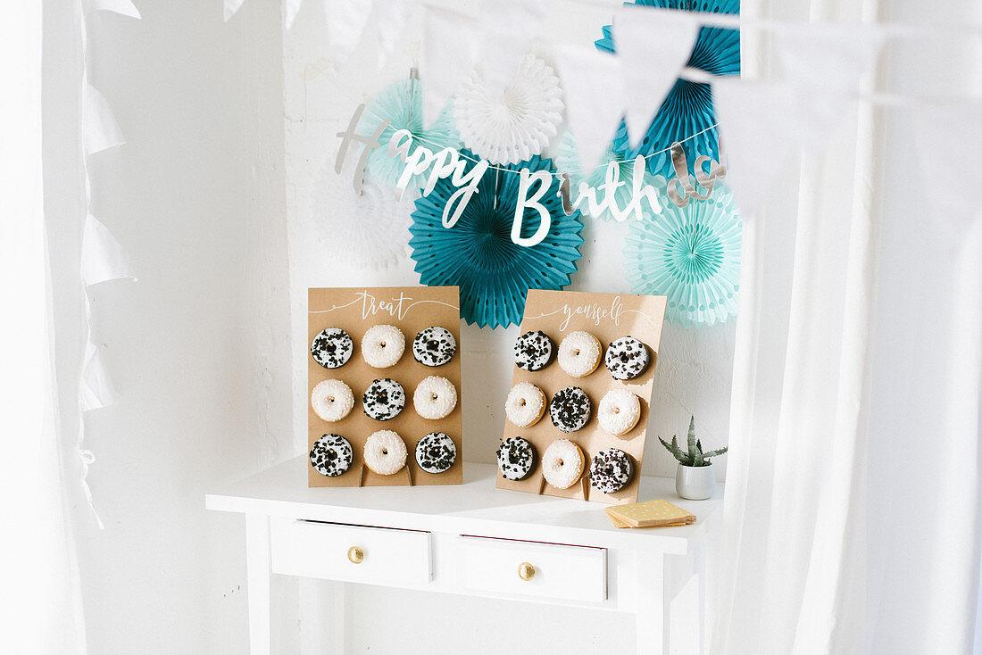 Birthday garland and paper rosettes above handmade doughnut racks on table