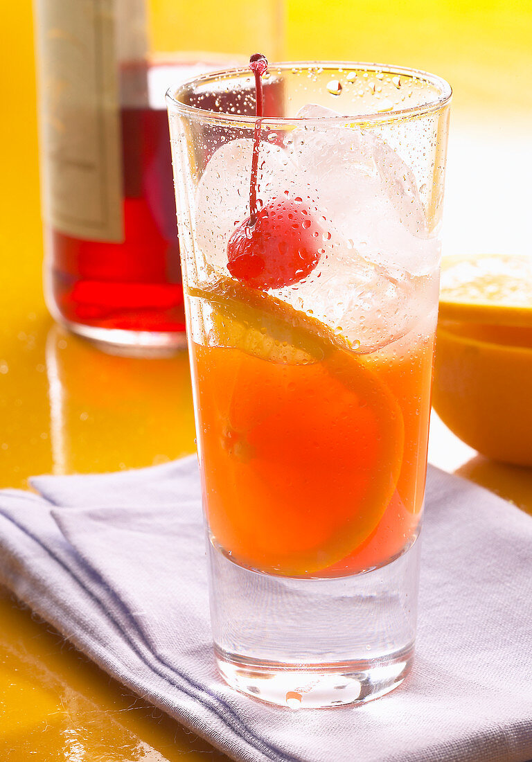 A classic Longdrink cocktail made with Campari, freshly squeezed orange juice, ice, orange slices, and cocktail cherries