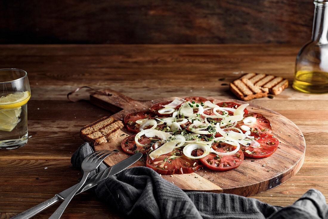 Carpaccio salad with kumato tomatoes, onion, parmesan cheese, fresh thyme