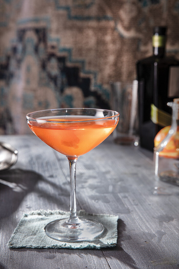 Gin martini cocktail with blueish table and carpet in background