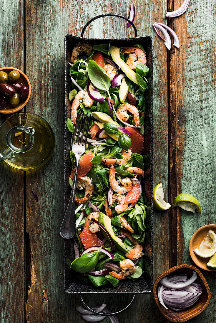 Salad with shrimp, red onion, pink grapefruit, avocado, lamb s lettuce, olives and basil