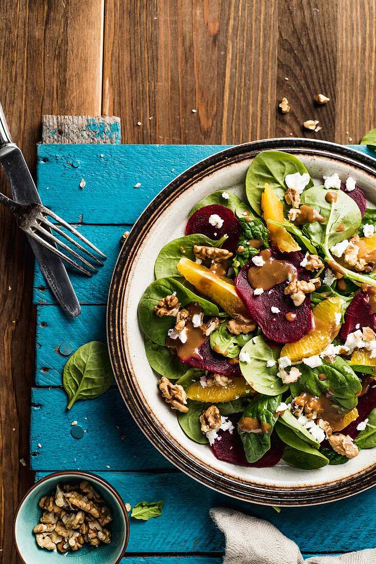 Spinach salad with beets, italian nuts, feta cheese, oranges and mustard vinaigrette sauce