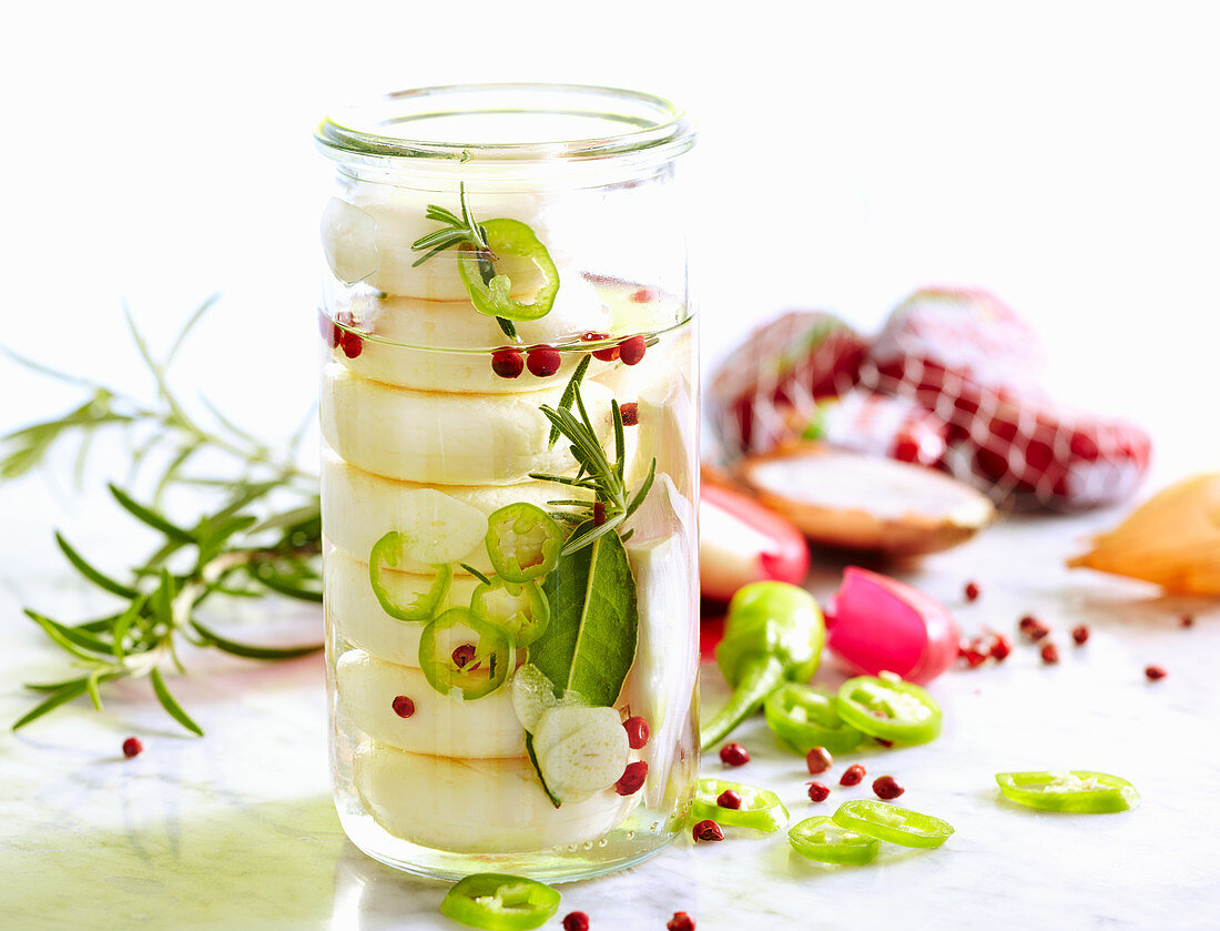 Babybel cheese pickled in oil with fresh herbs, jalapenos, pink pepper and bay leaves
