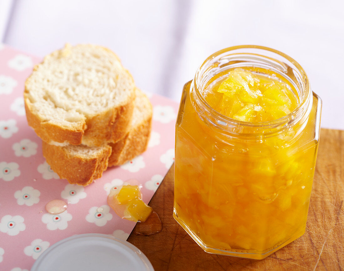 Homemade pineapple and ginger jam in a screw-top jar with bagette