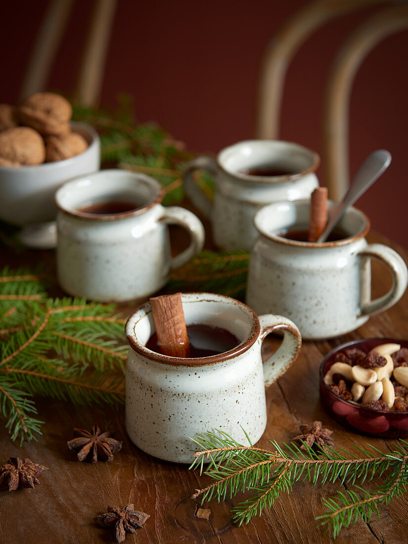 Rustic cups of mulled wine with cinnamon sticks