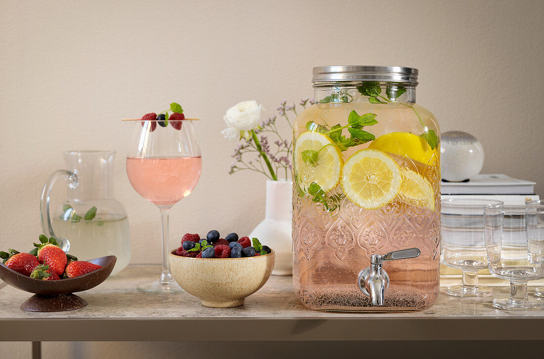 A refreshing drink with lemon slices in a drinks dispenser on a table with berries and a cocktail