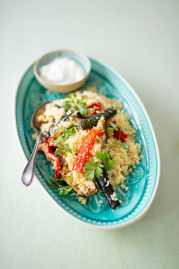 Couscous with vegetables and mint yogurt on a tray