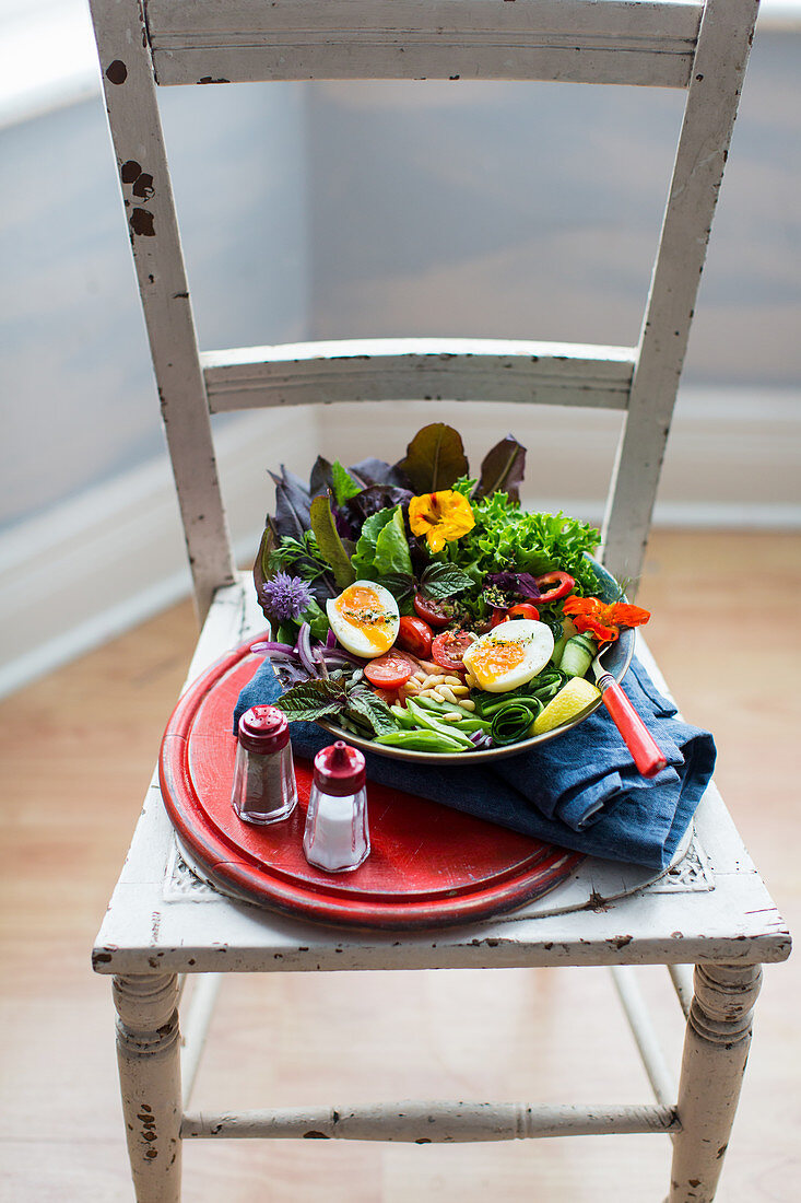 A mixed leaf salad with vegetables, edible flowers and poached eggs