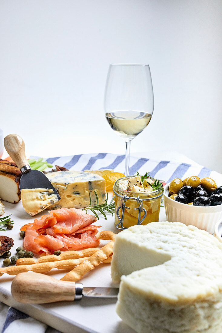 A Mediterranean appetizer platter with cheese, fish, olives and white wine