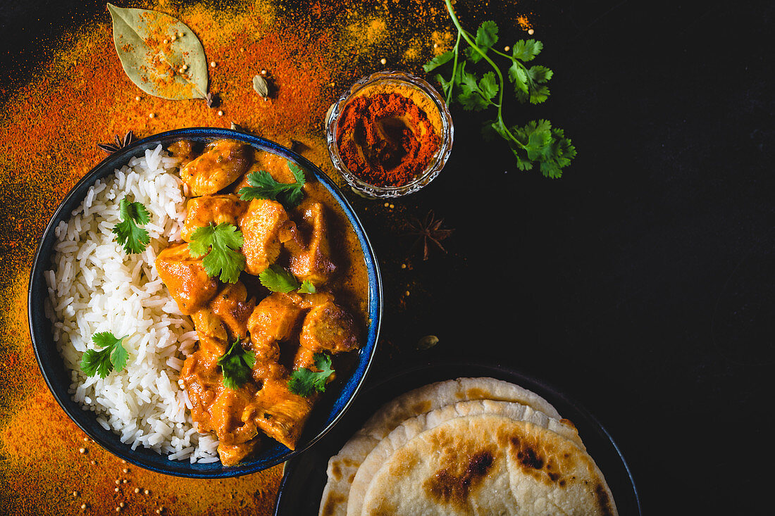 Indian Butter chicken with basmati rice in bowl, spices, naan bread
