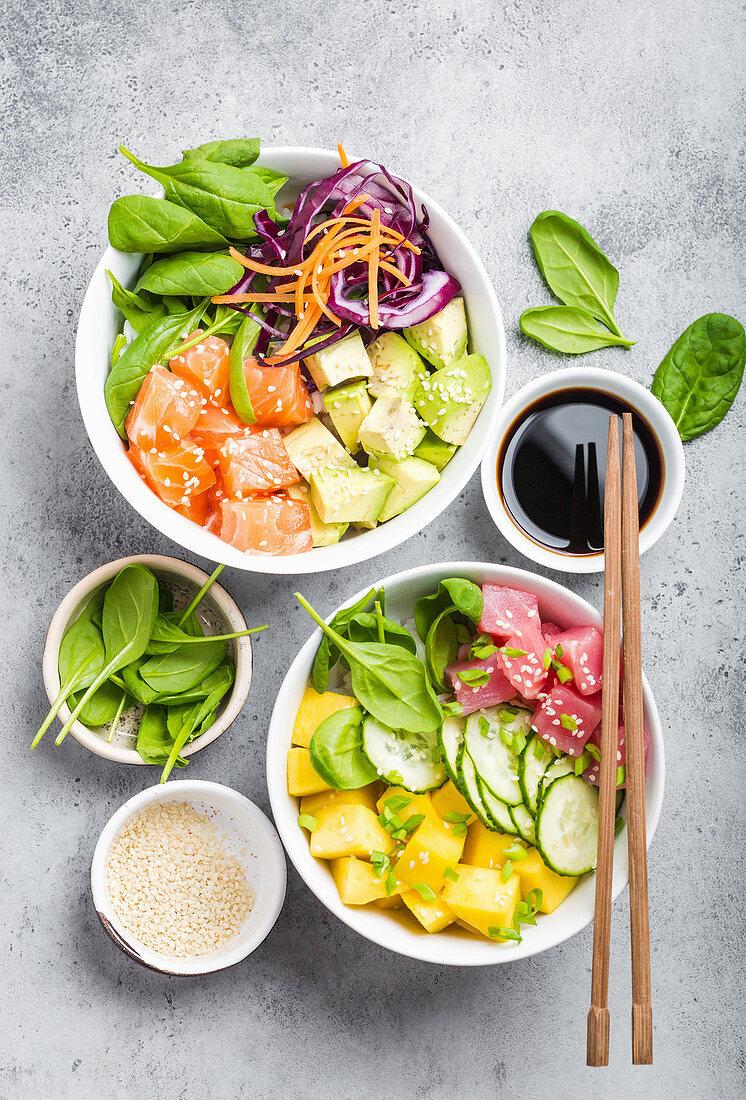Two assorted poke bowls, raw tuna, salmon, vegetables, fruit