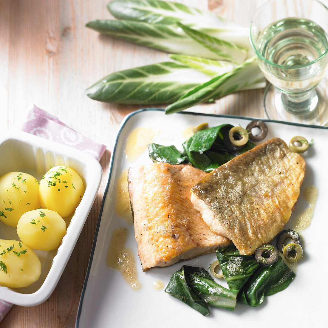 Fried char with lemon butter on a bed of chard and green olives