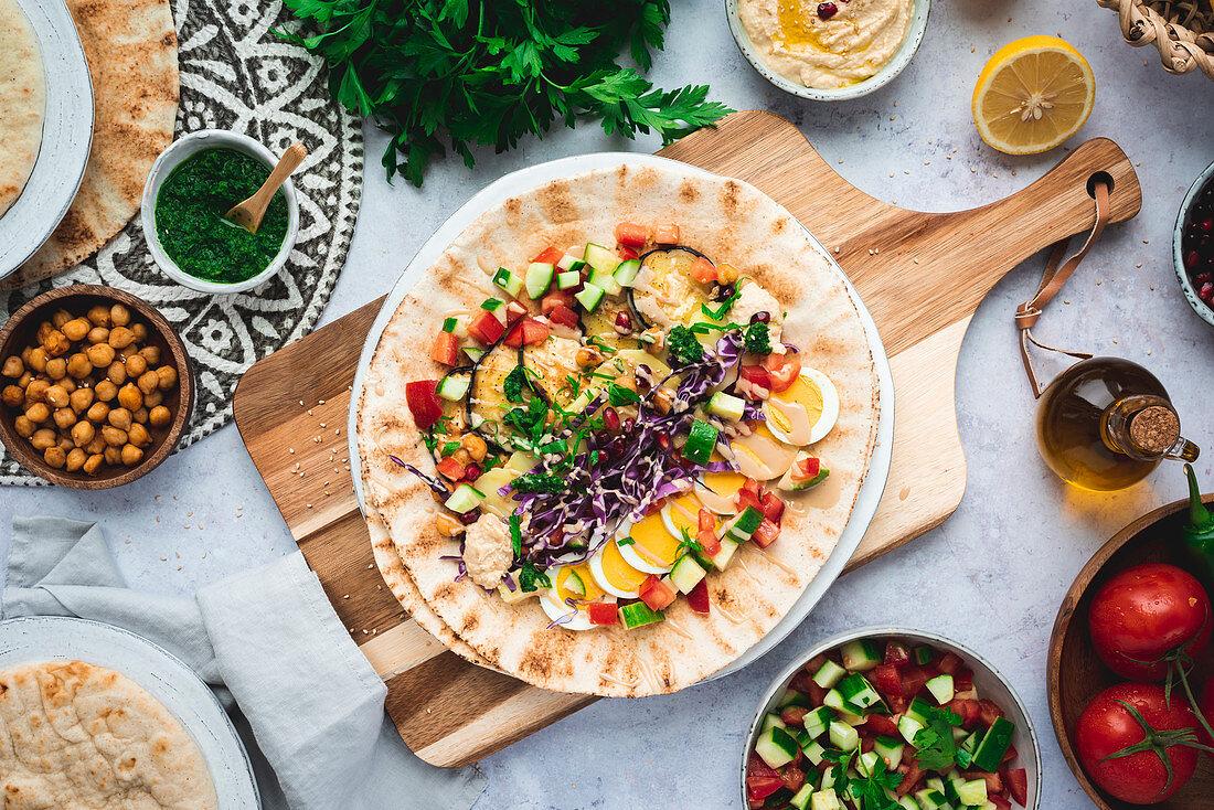 Sabich - Israeli street food in pita on a wooden board