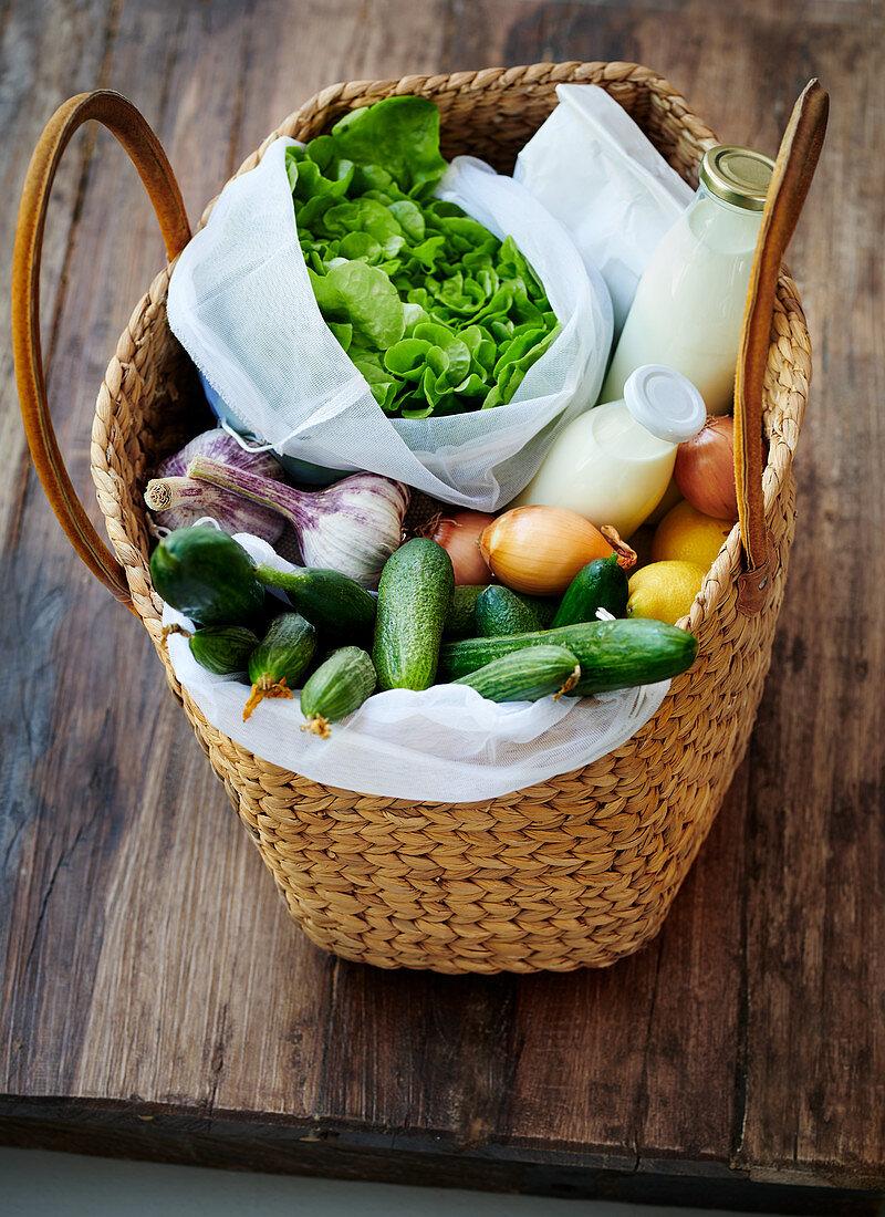 A basket bag with lettuce, vegetables, lemons, milk, cream and oatmeal