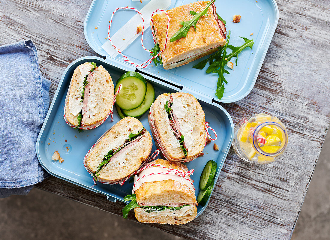 Baguette sandwiches with meatloaf, horseradish, cream cheese and arugula in a lunchbox