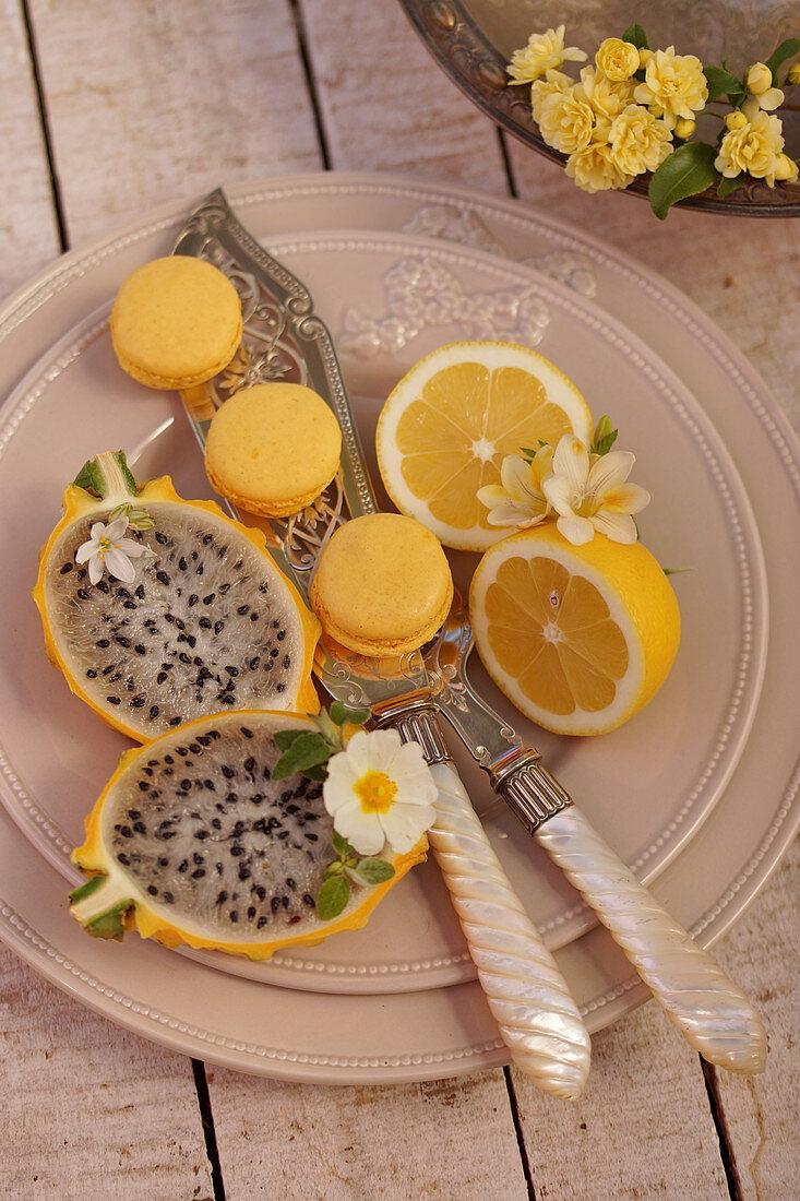 Lemon macarons, yellow dragon fruit and halved lemons on a plate