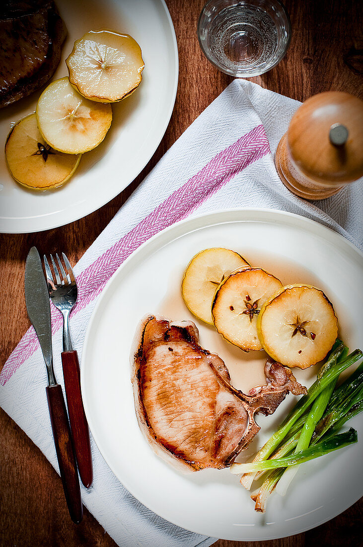 Pork chop with caramelised apple slices and fried spring onions