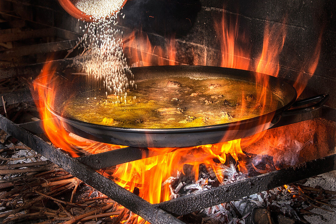 Adding rice into big iron pan with boiling broth for cooking paella over open fire with wood