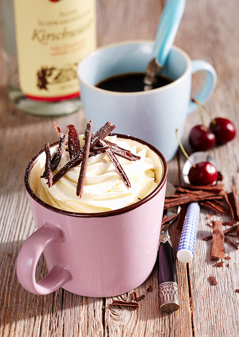 Black Forest coffee with whipped cream, kirsch, vanilla and chocolate chips in a pink enamel cup