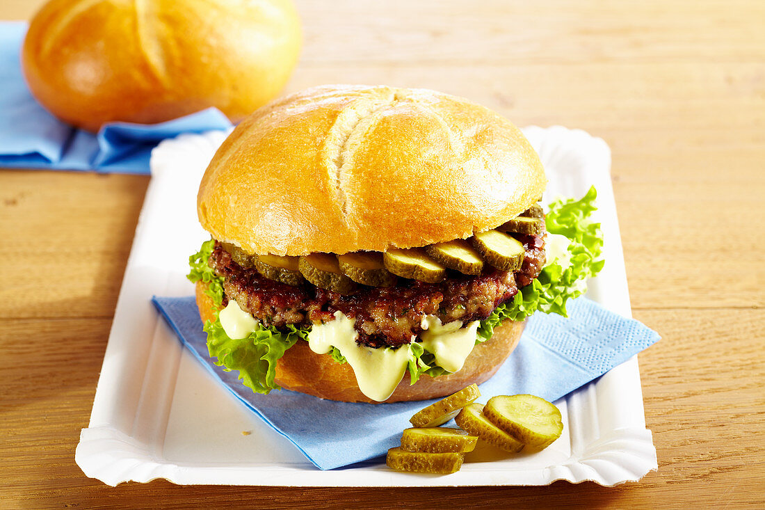 Meat patty roll with cheese cream and gherkins